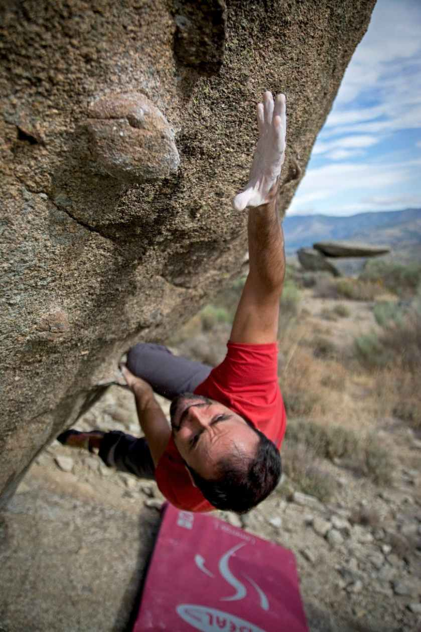 man climbing on gray concrete peak at daytime